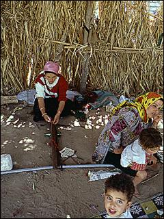 Gheita woman weaving w/ coke bottle