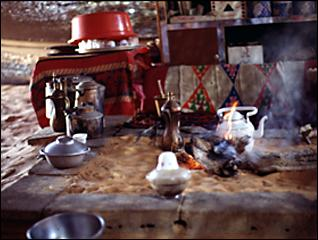 hearth in tent with fire, pans, and teapots